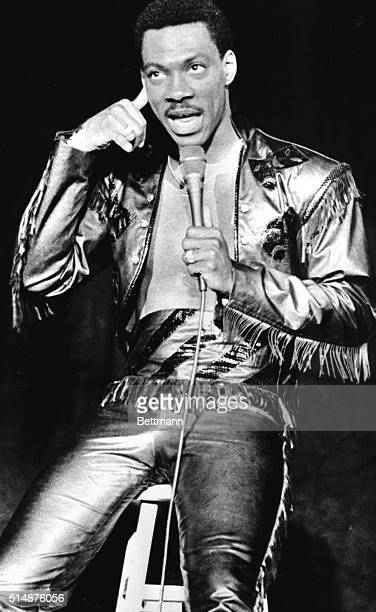 Comedian and movie star Eddie Murphy imitates Bill Cosby during a standup comedy performance in Binghampton He wears one of the tight fringed leather...