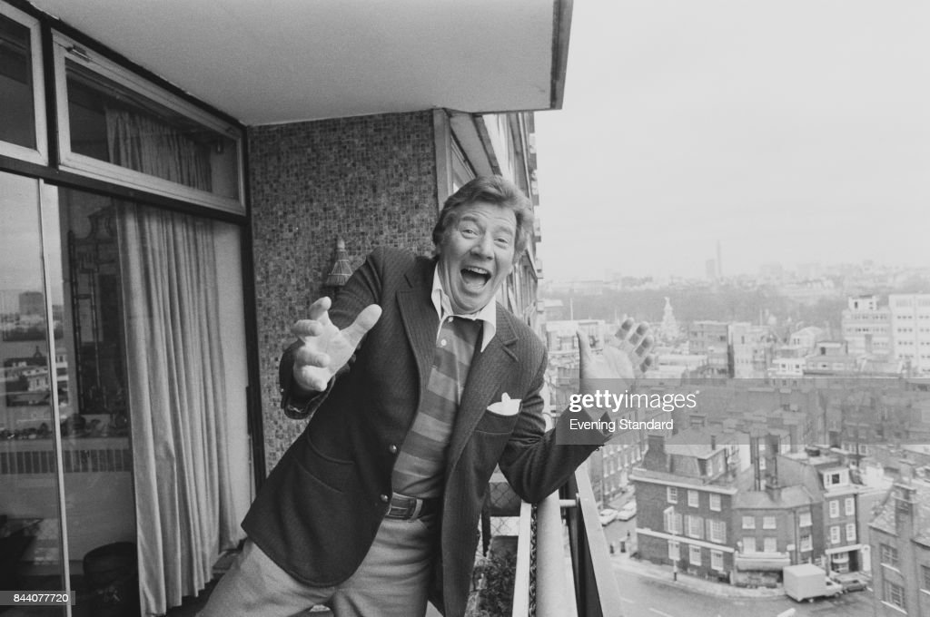 Comedian and performer Max Bygraves (1922 - 2012) stands in a funny pose from a balcony, 29th March 1978.