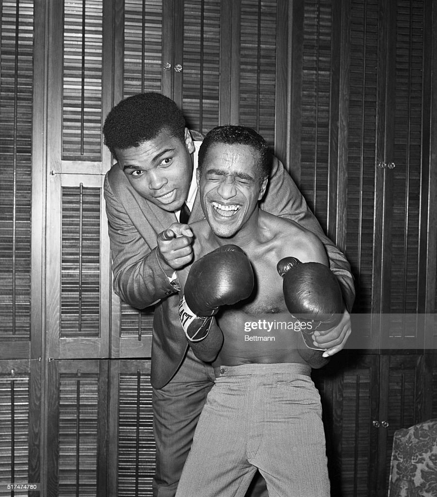 Comedian and singer Sammy Davis, Jr. gets some boxing pointers from Heavyweight Champion Cassias Clay (L) at the Majestic Theatre following Davis's performance in Golden Bay. Earlier, Clay had signed a contract for radio rights for his upcoming fight with Sonny Liston.