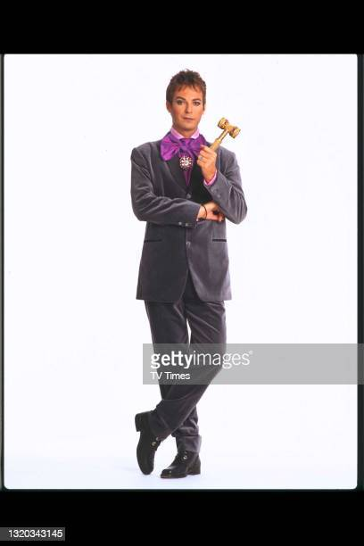 Comedian and television presenter Julian Clary photographed with the gavel from his light entertainment series All Rise for Julian Clary, circa 1997.