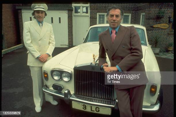 Comedian and television presenter photographed next to his Rolls Royce and chauffeur, circa 1977.