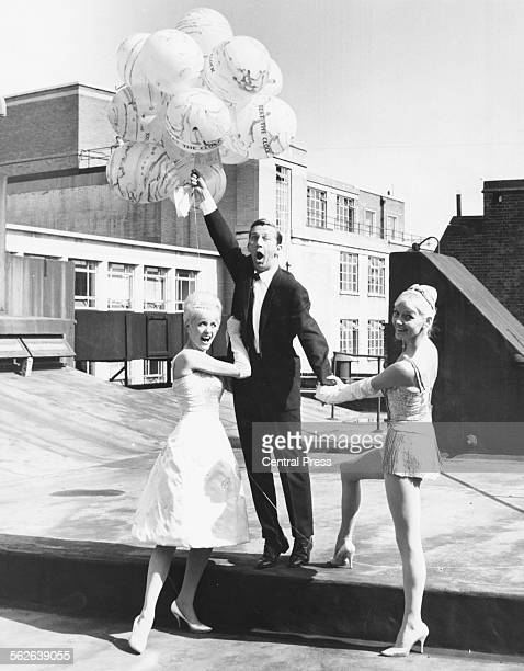 Comedian and variety performer Norman Vaughan posing with London Palladium girls Angela Bracewell and Audrey Bayley as he pretends to get carries...
