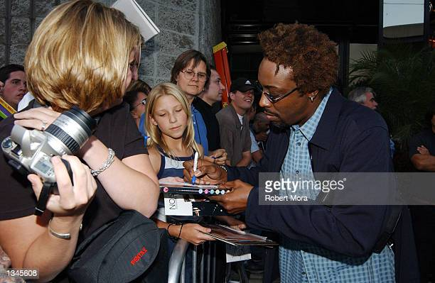 "Comedian Arsenio Hall signs autographs prior to the premiere of ""Serving Sara"" at the Samuel Goldwyn Theater on August 20, 2002 in Beverly Hills,..."