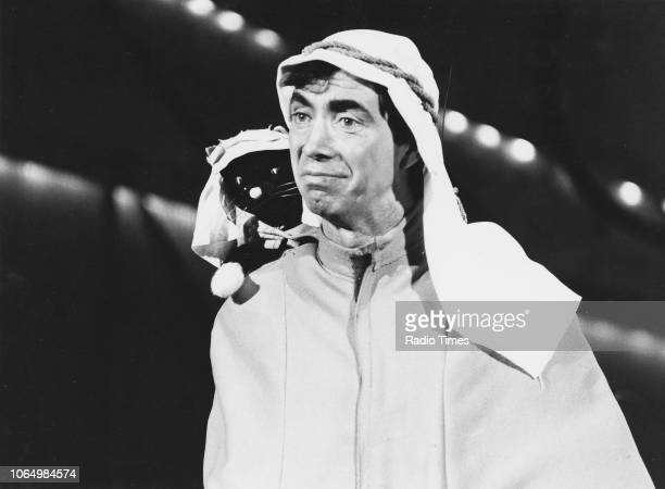 Comedian Bernie Clifton performing with a toy cat on his shoulder, November 28th 1976.