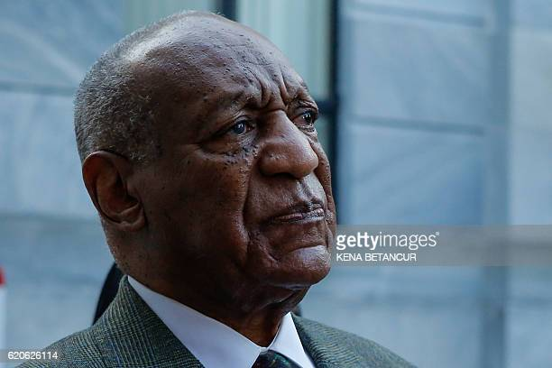 Comedian Bill Cosby pauses as he listen to his defense lawyer Angela Agrusa while she speaks with members of the media outside the Montgomery County...