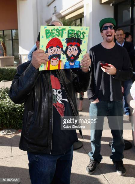 Comedian Cheech Marin holds up an artwork created by a fan depicting the comedy duo Cheech Marin and Tommy Chong during a meet and greet to introduce...