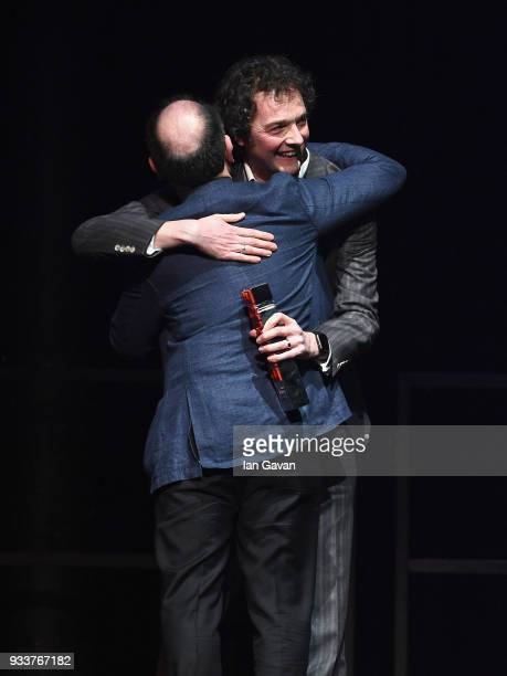 Comedian Chris Addison presents actor Armando Iannucci with the award for Best Comedy for 'Death of Stalin' on stage during the Rakuten TV EMPIRE...