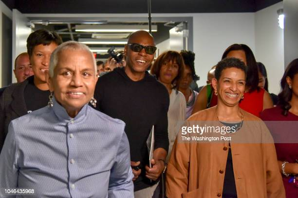 Comedian Dave Chappelle C passes through the hallways of Duke Ellington School of the Arts with DC mayor Muriel Bowser L and Peggy Cooper Cafritz...