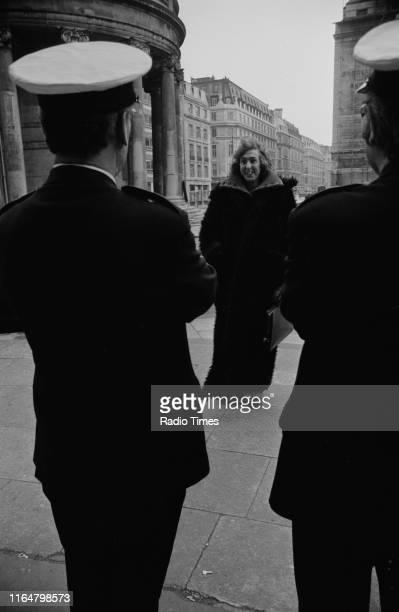 Comedian Eric Idle greeting two security guards as he prepares to perform on the roof of BBC Broadcasting House for the BBC radio special 'Radio 5...