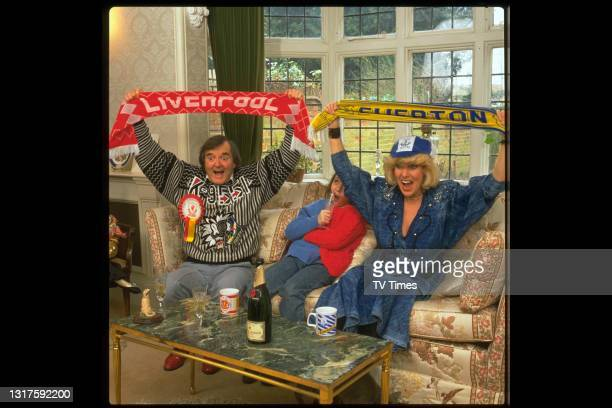 Comedian Faith Brown photographed watching a football match at home with her family, circa 1988.