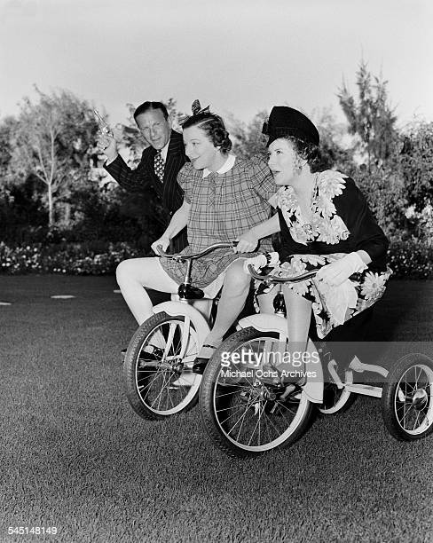 Comedian Fanny Brice races tricycles against Gracie Allen as George Burns fires the starting gun during her birthday party in Los Angeles California