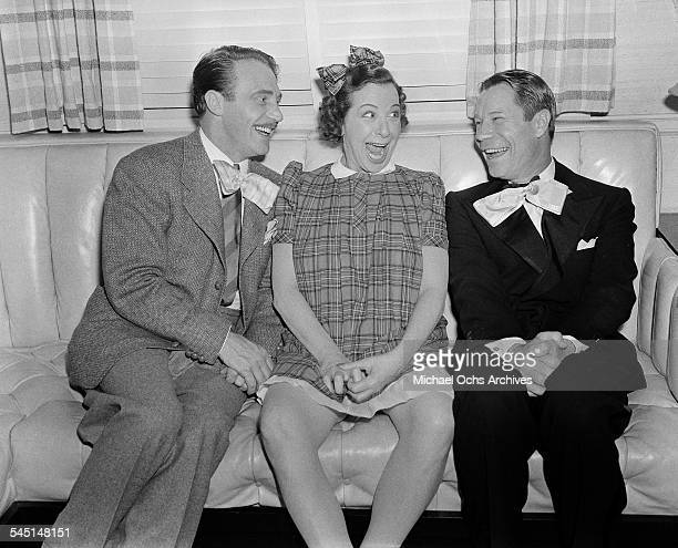 Comedian Fanny Brice sits with friends Joe E Brown during her birthday party in Los Angeles California