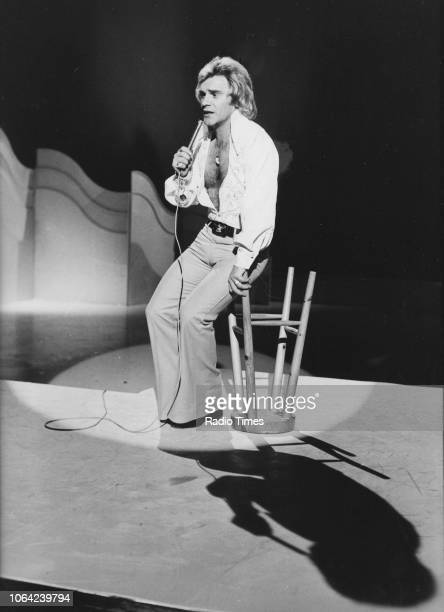 Comedian Freddie Starr sitting on an overturned bar stool while performing on stage January 27th 1976