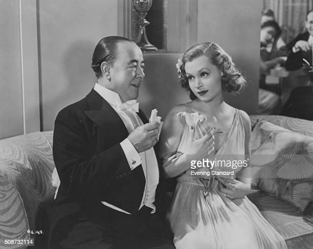 Comedian George Robey and actress Lilli Palmer sitting together in a scene from the film 'A Girl Must Live' 1939.