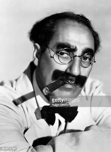 Comedian Groucho Marx with his trademark cigar and greasepaint facial hair