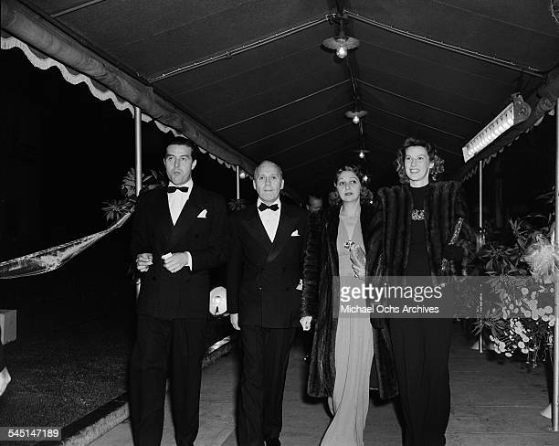 Comedian Jack Benny and his wife Mary Livingstone walk between Welsh actor Ray Midland and his wife Muriel Weber as they attend an event in Los...