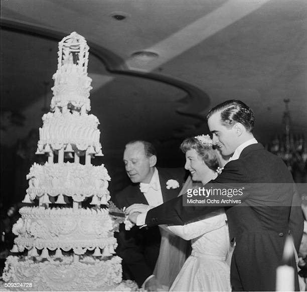 Comedian Jack Benny looks on as his daughter Joan Benny and her newly husband Seth Baker cut their wedding cake in Beverly Hills Hotel in Beverly...