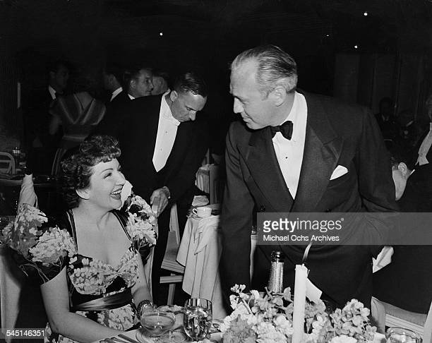 Comedian Jack Benny talks with actress Claudette Colbert during an event in Los Angeles California