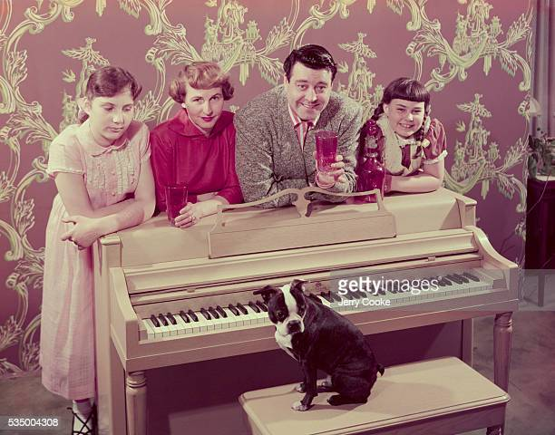 Comedian Jackie Gleason poses at the piano with his wife Genevieve daughters Linda and Geraldine and their Boston terrier