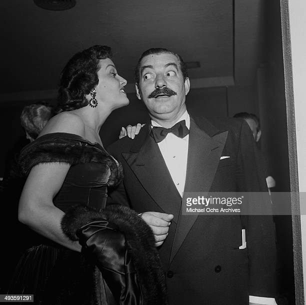 Comedian Jerry Colonna gets an earful from Jane Russell a during the International Press Club Awards in Los Angeles California