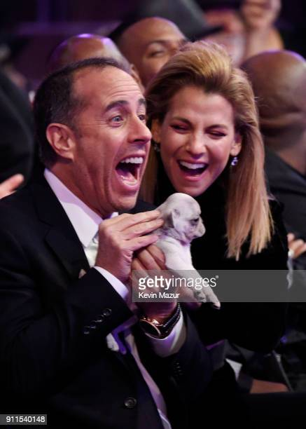 Comedian Jerry Seinfeld receives a consolation puppy during the 60th Annual GRAMMY Awards at Madison Square Garden on January 28 2018 in New York City