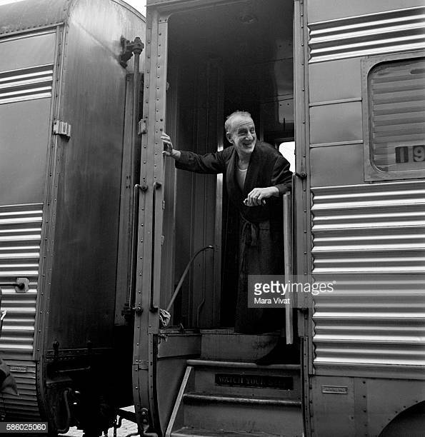 Comedian Jimmy Durante stands in the doorway of a railroad car in his dressing gown