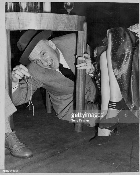 Comedian Jimmy 'Schnozzle' Durante, joking around under a table at a press reception at the Prince of Wales Theatre, London, April 29th 1952.
