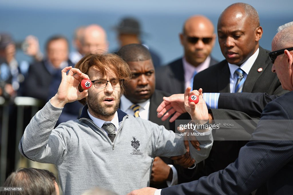 Comedian Lee Nelson is taken away by security while holding golf balls stamped with swastika as he protests against Presumptive Republican nominee for US president Donald Trump a he gave a press conference on the 9th tee at his Trump Turnberry Resort on June 24, 2016 in Ayr, Scotland. Mr Trump arrived to officially open his golf resort which has undergone an eight month refurbishment as part of an investment thought to be worth in the region of two hundred million pounds.
