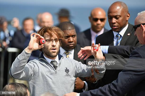 Comedian Lee Nelson is taken away by security while holding golf balls stamped with swastika as he protests against Presumptive Republican nominee...