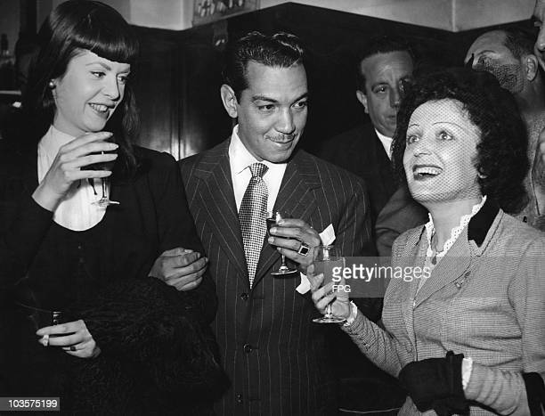 Comedian Mario Moreno also known as Cantinflas toasts singer Edith Piaf as he and his lady friend visit the Ciudad Luz nightclub in Paris France 6...