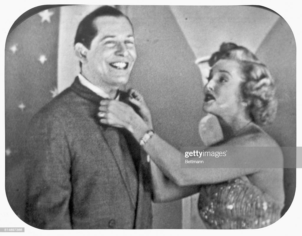 Comedian Milton Berle gets his jacket straightened by actress Vivian Blaine during an unidentified television program. Undated photograph.