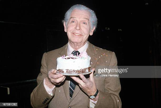 """Comedian Milton Berle poses with a birthday cake while rehearsing the Off Broadway play """"Good Night, Grandpa"""" January 17, 1983 in New York City."""