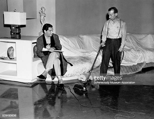 Comedian Milton Berle watches a custodian use a GE floor polisher on a set at RKO MotionPicture Studios