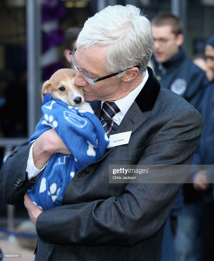 Comedian Paul O'Grady hugs a lurcher-cross puppy called 'Mince Pie' as she visits Battersea Dog and Cats Home on December 12, 2012 in London, England. The Duchess of Cornwall as patron of Battersea Dog and Cats home visited with her two Jack Russell terriers Beth, a 3 month old who came to Battersea as an unwanted puppy in August 2011 and Bluebell a nine week old stray who was found wandering in a London Park in September 2012.