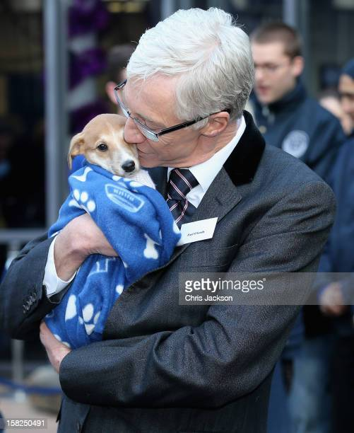 Comedian Paul O'Grady hugs a lurchercross puppy called 'Mince Pie' as she visits Battersea Dog and Cats Home on December 12 2012 in London England...