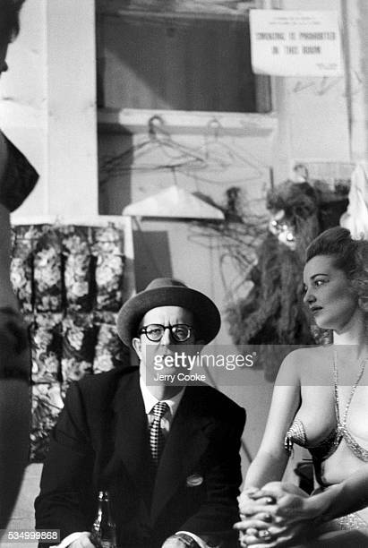 Comedian Phil Silvers relaxes with strippers in the dressing room of the Old Howard Burlesque House