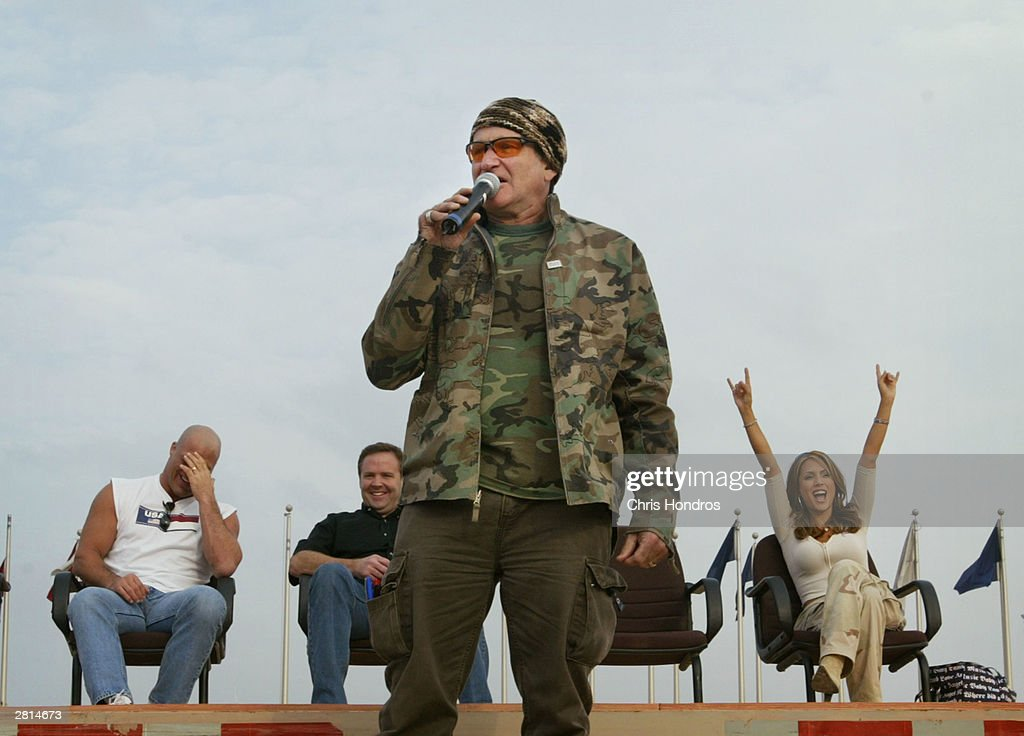 Comedian Robin Williams entertains troops along with other celebrities December 16, 2003 in Baghdad, Iraq. Williams poked fun at military life and world politics during his routine for hundreds of troops.