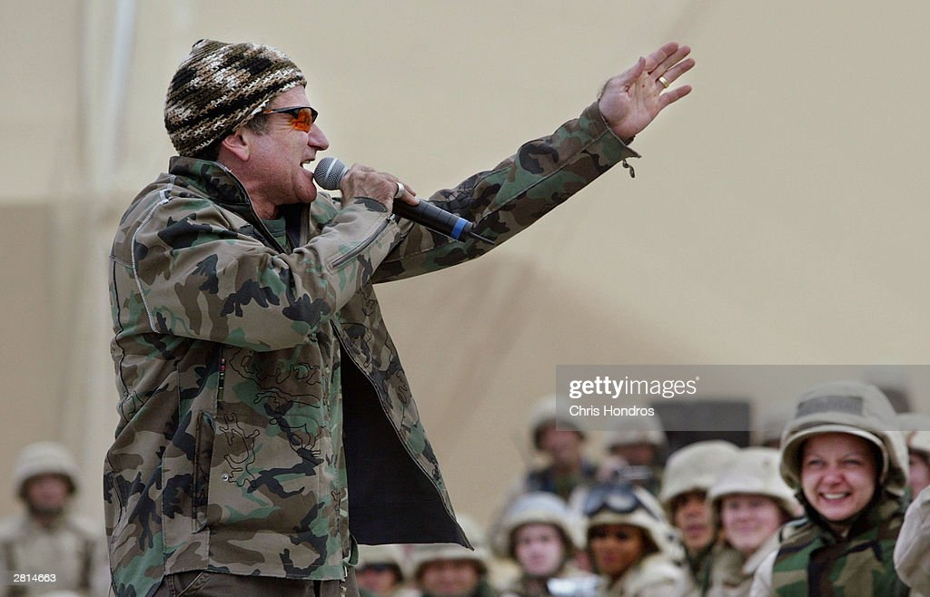 Comedian Robin Williams takes a picture with GI's camera as he entertains troops at Baghdad airport December 16, 2003 in Baghdad, Iraq. Williams poked fun at military life and world politics during his routine for hundreds of troops.