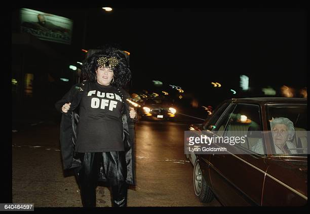 Comedian Roseanne stands in traffic wearing a Fuck Off Tshirt and leather pants