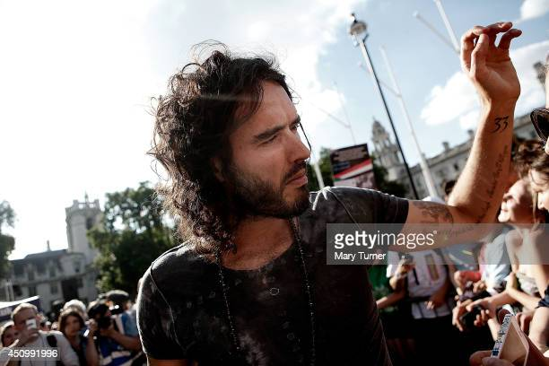 Comedian Russell Brand poses for photographs with fans as he meets members of a crowd of thousands that gathered in Parliament Square to protest on...