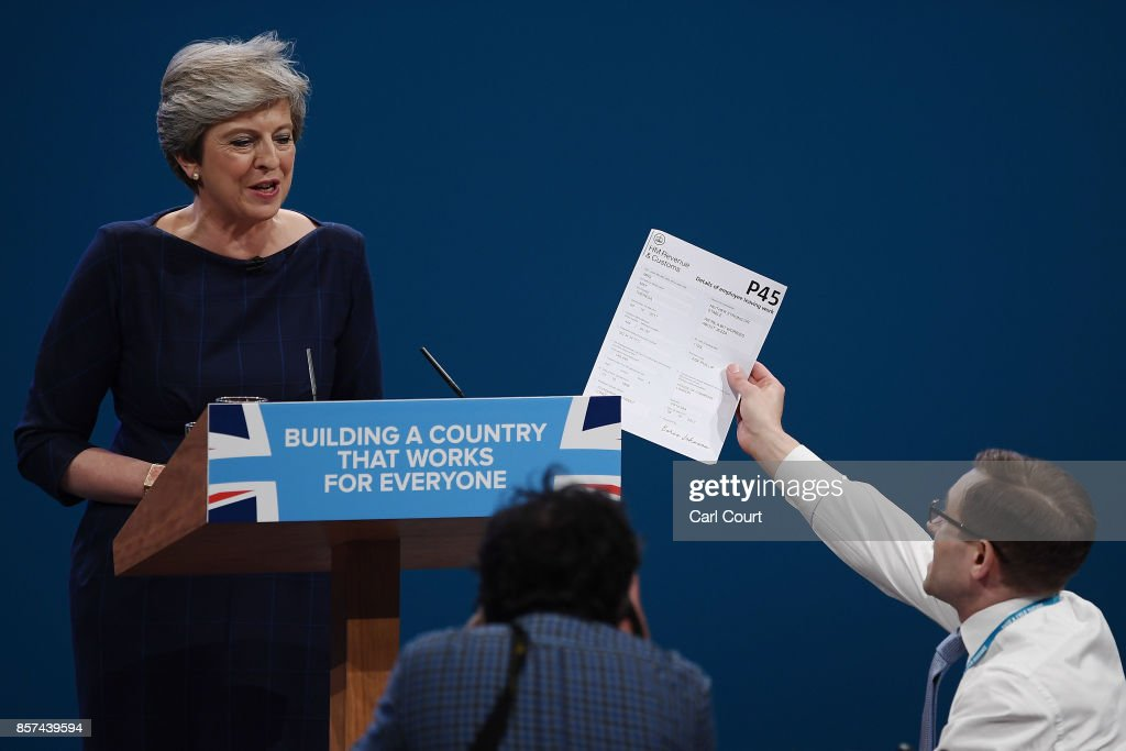 Comedian Simon Brodkin, aka prankster Lee Nelson, hands Prime Minister Theresa May a P45 during her keynote speech to delegates and party members on the last day of the Conservative Party Conference at Manchester Central on October 4, 2017 in Manchester, England. The prime minister rallied members and called for the party to 'shape up' and 'go forward together'. Theresa May also announced a major programme to build council houses and a cap on energy prices.
