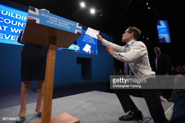 Comedian Simon Brodkin, aka prankster Lee Nelson, hands Prime Minister Theresa May a P45 during her keynote speech to delegates and party members on...