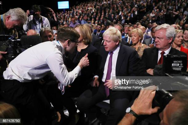 Comedian Simon Brodkin gives the thumbs up to Foreign Secretary Boris Johnson after handing Prime Minister Theresa May a P45 during her keynote...