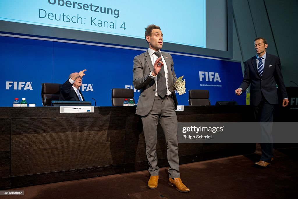 Comedian Simon Brodkin prepares to attack FIFA President Joseph S. Blatter (L) with money during a press conference at the Extraordinary FIFA Executive Committee Meeting at the FIFA headquarters on July 20, 2015 in Zurich, Switzerland.