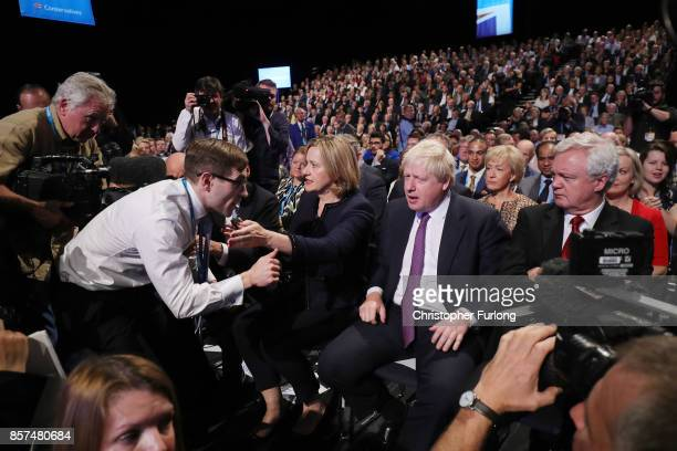 Comedian Simon Brodkin speaks to Foreign Secretary Boris Johnson after handing Prime Minister Theresa May a P45 during her keynote speech to...