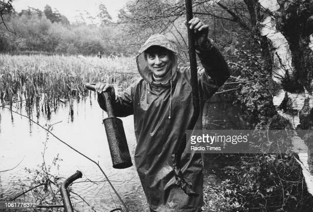 Comedian Spike Milligan pictured recovering scrap metal from a pond photographed for Radio Times in connection with the television show 'Down to...