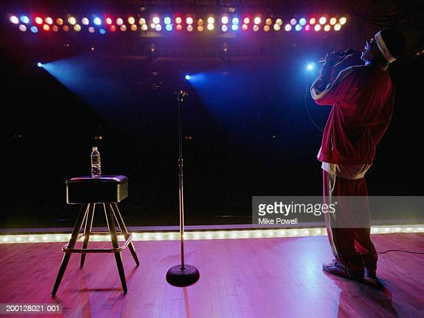 Comedian standing on stage, laughing , rear view