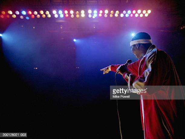comedian standing on stage pointing towards audience, rear view - comedian stock pictures, royalty-free photos & images
