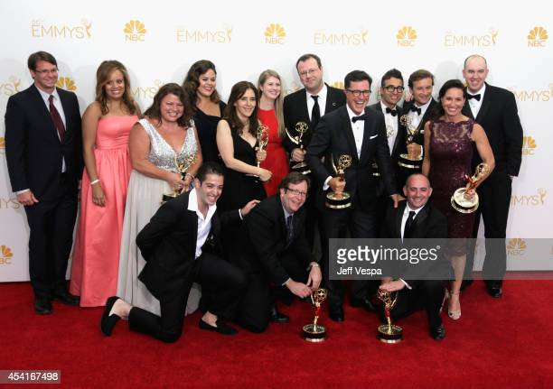 Comedian Stephen Colbert and crew members of 'The Colbert Report' pose in the press room during the 66th Annual Primetime Emmy Awards at Nokia...