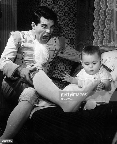 Comedian Ted Rogers dressed as Buttons for a rehearsal of the pantomime Cinderella at the Adelphi Theatre the Strand London keeps his baby daughter...